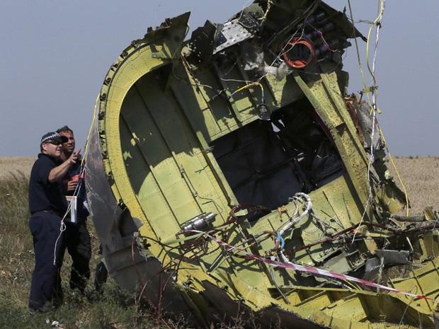 Especialistas inspecionam destroços no local onde o MH17 da Malaysia Airlines caiu, no leste da Ucrânia. Confrontos nas proximidades fizeram a equipe abandonar parte do local (Foto: Sergei Karpukhin/Reuters)