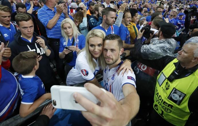 Gylfi Sigurdsson tira selfie com a esposa Alexandra Ivarsdottir no meio da torcida da Islândia (Foto: REUTERS/Carl Recine)