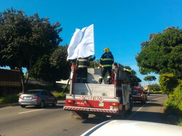 Bandeira branca é levada em caminhão do Corpo de Bombeiros durante cortejo de Ana Clara, em Goiânia, Goiás (Foto: Vanessa Martins/G1)