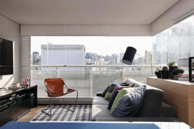 Solução de marcenaria: o aparador atrás do sofá esconde a unidade condensadora de ar-condicionado, o que garantiu o aproveitamento máximo da varanda, fechada com vidro e integrada à sala de estar (Foto: Mariana Orsi / Editora Globo)