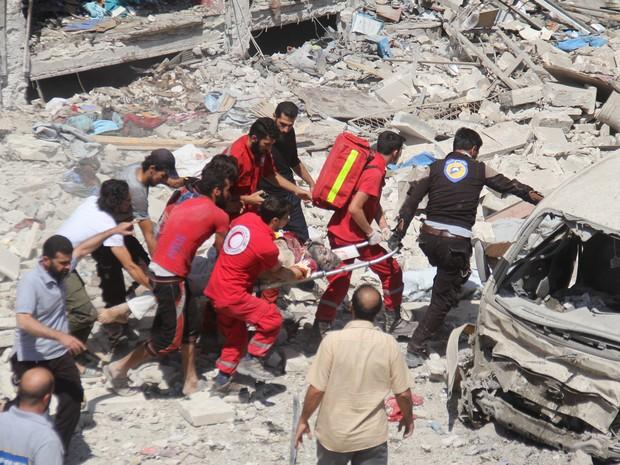 Vítima de bombardeio é resgatada em Idlib, Síria; guerra civil forçou 11 milhões a deixarem suas casas e matou ao menos 250 mil (Foto: OMAR HAJ KADOUR / AFP)