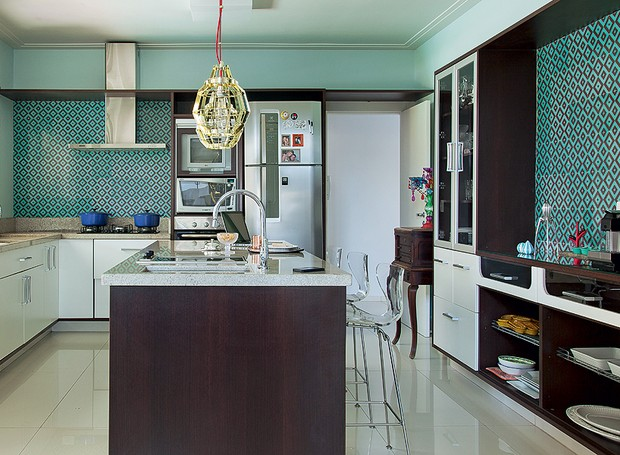 Azulejos retrô esverdeados revestem a cozinha projetada pela arquiteta Andrea Murao. A cor está presente em outras partes da decoração, como o sofá e a porta de correr (Foto: Cacá Bratke/Casa e Jardim)