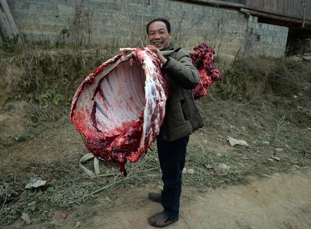 Homem sorri ao carregar 'banquete cru' para casa na China (Foto: Mark Ralston/AFP)