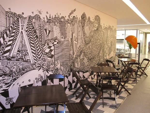 Mural do novo escritório do Google Brasil, em São Paulo, com mesas na frente, feito pelo grafiteiro Rolim. (Foto: Amanda Demetrio/G1)