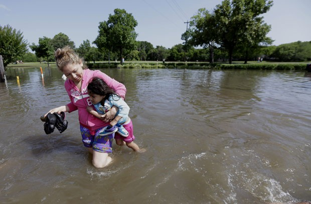 Mulher carrega criança em meio a enchente em Houston, no Texas, nesta terça-feira (26) (Foto: AP Photo/David J. Phillip)