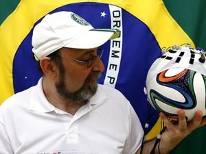 Cientista Miguel Nicolelis segura uma bola de futebol com uma toca de eletrodos nesta quarta-feira (21) (Foto: Reuters/Paulo Whitaker)