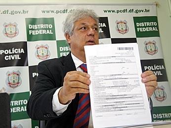 Delegado João Carlos Lóssio mostra um dos documentos apresentados pelos suspeitos (Foto: Ricardo Moreira / G1)