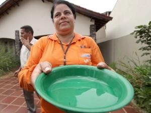 Agente de saúde mostra vasinha com larvas de mosquito da dengue em imóvel que estava fechado. (Foto: Divulgação/PMCG)