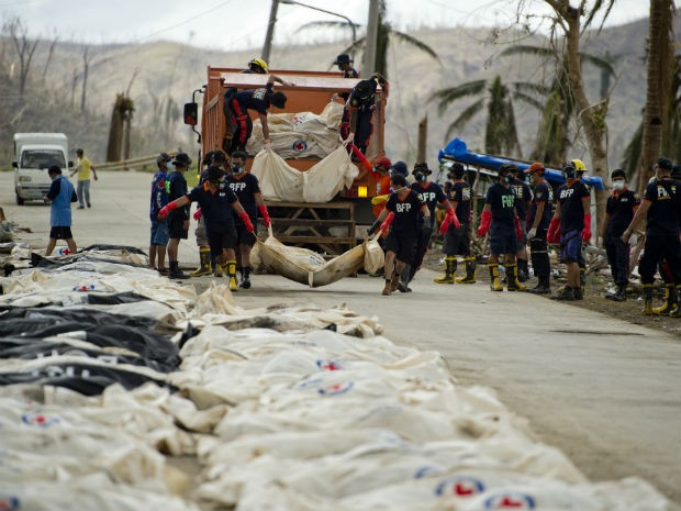 Bombeiros recolhem corpos recolhidos nos escombros após passagem de tufão nas Filipinas (Foto: Odd Andersen/AFP)