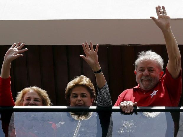 A presidente Dilma Rousseff acena ao lado do ex-presidente Luiz Inácio Lula da Silva na varanda do apartamento de Lula em São Bernardo do Campo, em SP (Foto: Paulo Whitaker/Reuters)