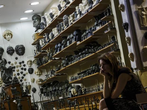 Vendedora espera por clientes em uma loja de souvenirs em Atenas (Foto: Daniel Ochoa de Olza / AP)