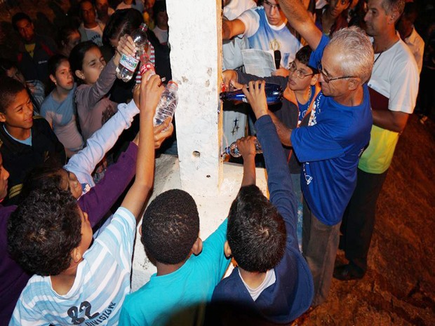Moradores jogaram água nos pés da cruz (Foto: Marcelo Praxesdes/Divulgação)