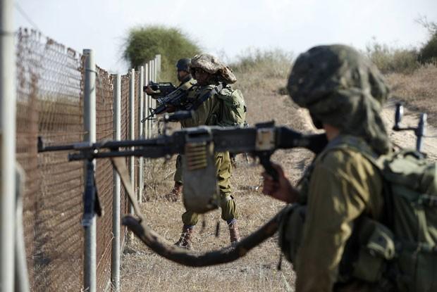 Soldados israelenses se posicionam ao lado de cerca na cidade de Sderot durante infiltração de militantes palestinos nesta segunda-feira (21) (Foto: Baz Ratner/Reuters)