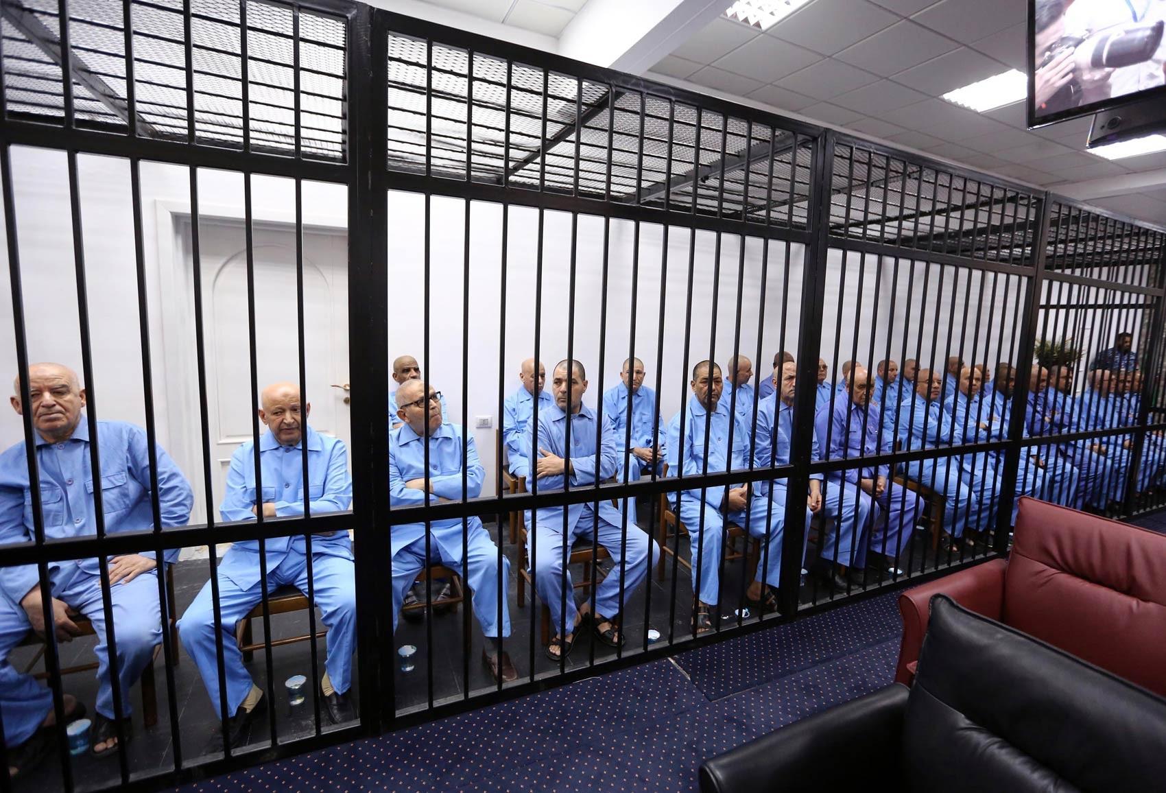 Antigos colaboradores do ditador deposto Muammar Kadhafi são mantidos atrás das grades dos acusados durante julgamento em Trípoli, Líbia. O tribunal condenou à morte Seif al Islam Kadhafi, o filho mais conhecido do ex-ditador, além de 8 dos colaboradores (Foto: Mahmud Turkia/AFP)