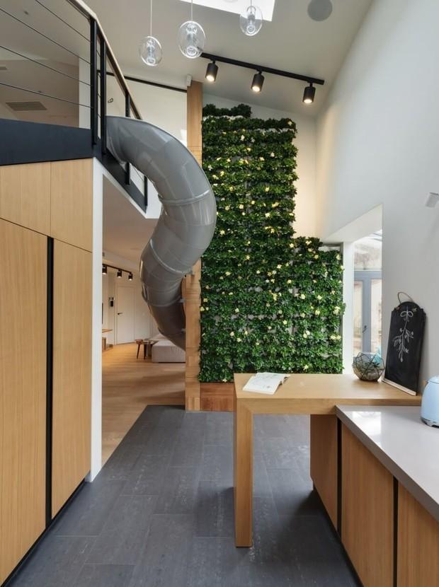 O escorregador parte da lateral da escada e passa ao lado da parede com o jardim vertical  (Foto: Ki Design)