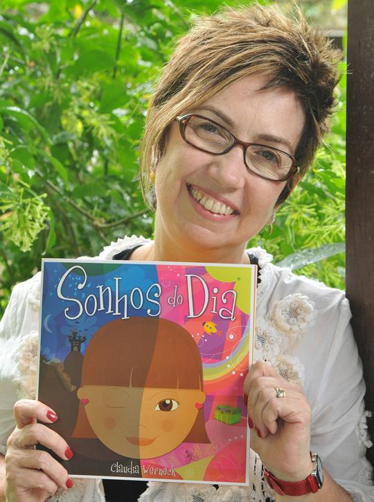 A jornalista e escritora Claudia Werneck com  um de seus livros (Foto: Divulgação)