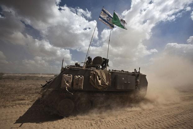 Soldados israelenses andam em tanque do lado de fora da Faixa de Gaza nesta terça-feira (15) (Foto: Nir Elias/Reuters)