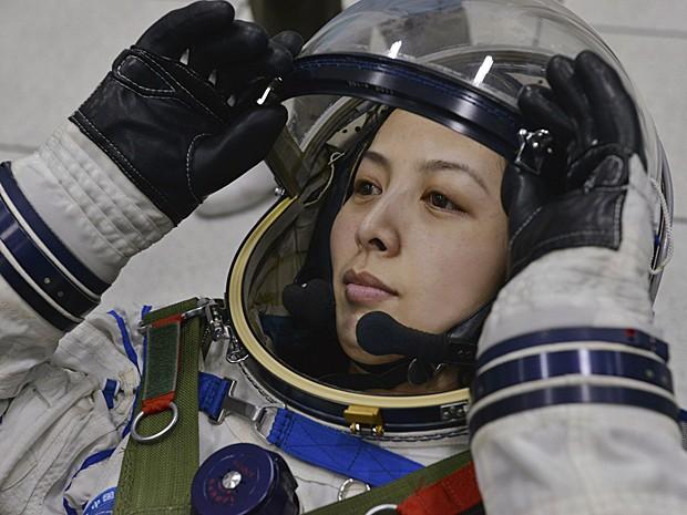 Astronauta chinesa Wang Yaping ajusta o capacete espacial durante treinamento em Pequim no sábado (8) (Foto: Reuters)