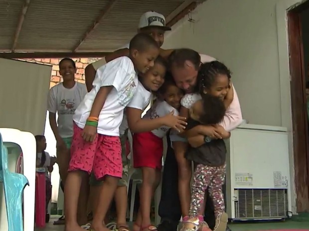 Sérgio abraça crianças que ajuda na Bahia (Foto: Reprodução/TV Bahia)