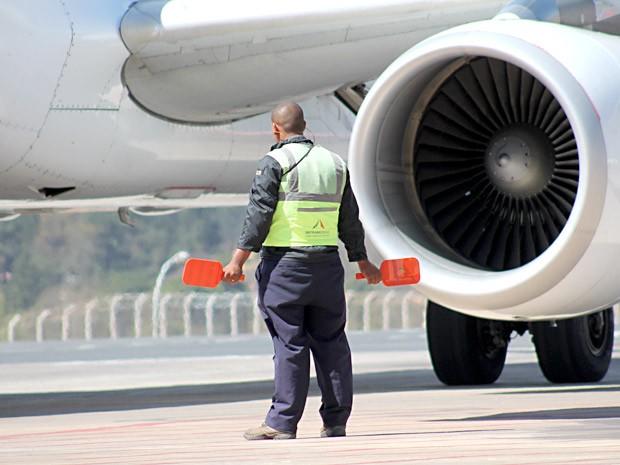 Funcionário da Inframerica orienta aeronave na pista do Aeroporto JK, em Brasília (Foto: Jua Pita/Inframerica/DIvulgação)