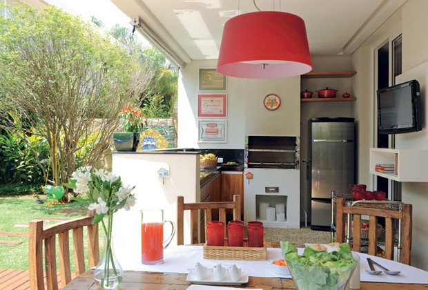 Integrada ao restante do terraço, a mesa de jantar foi garimpada pela proprietária em um antiquário, em Embu das artes. De estilo moderno, o pendente vermelho, da Lustreco, destaca-se na decoração. ao fundo, a churrasqueira da Casa das Lareiras (Foto: Casa e Jardim)