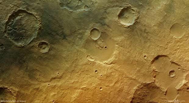 A cratera de 34 km de largura no canto superior esquerdo tem blocos largos de topo achatado chamados mesa. Esses blocos foram talhados a partir de sedimentos que originalmente encheram a cratera e que foram ali depositados durante uma inundação que cobriu toda a área. Com o tempo, sedimentos mais fracos foram erodidos, deixando um padrão aleatório de blocos mais fortes que permaneceram. (Foto: ESA/DLR/FU Berlin (G. Neukum))