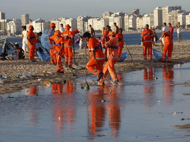 Garis limpam a praia de Copacabana após réveillon. (Foto: Severino Silva/Agência O Dia/Estadão Conteúdo)