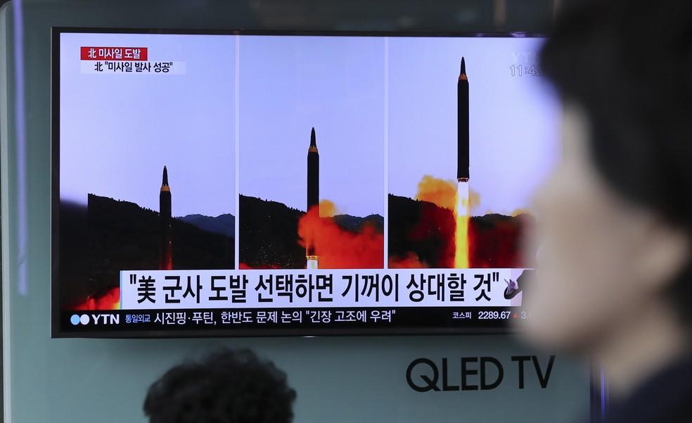 Mulher caminha próximo a TV que mostra noticiário na Coreia do Sul relatando lançamento do míssil no país vizinho (Foto: Lee Jin-man/AP)