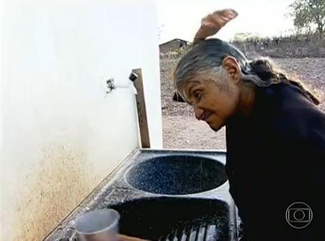 Dona  Delmindi toma banho de caneca no sertão (Foto: Rede Globo)