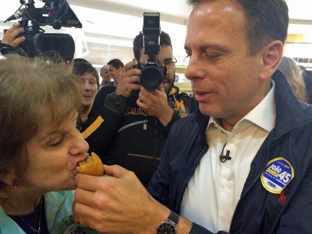 O candidato do PSDB à prefeitura de São Paulo, João Doria, oferece uma coxinha para uma eleitora em padaria no Tatuapé (Foto: Tahiane Stochero/G1)