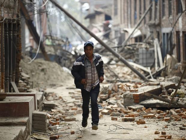 26/04 - Homem corre entre ruínas de prédios em Bhaktapur, após segundo tremor no domingo  (Foto: Navesh Chitrakar / Reuters)