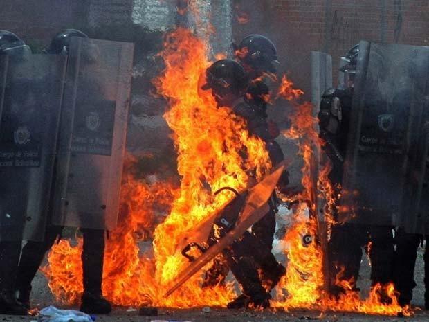 Fogo em policial foi provocado por lançamento de coquetel molotov por manifestantes, segundo agência France Presse, nesta segundafeira (25) (Foto: AFP PHOTO/GEORGE CASTELLANOS)
