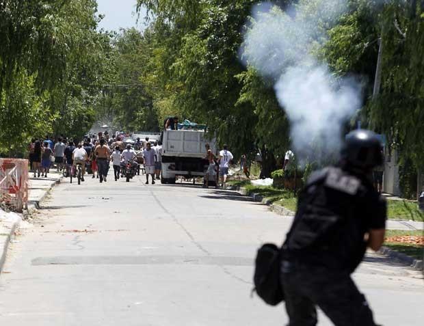 Policial enfrenta saqueadores em San Fernando, nos arredores de Buenos Aires, nesta sexta-feira (21) (Foto: Reuters)