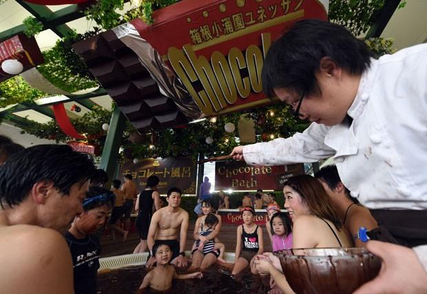 Usando uma roupa de chef confeiteiro, um dos funcionários do spa derrama chocolate nas banheiras do estabelecimento (Foto: Toshifumi Kitamura/AFP)