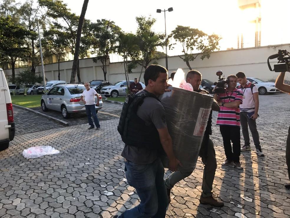 Agente chega a Cidade da Polícia com um aquecedor onde eram ocultos os fuzis (Foto: Henrique Coelho/G1)