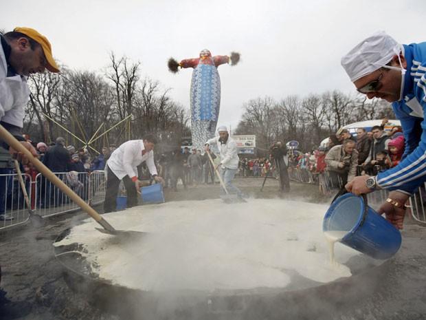 Homens preparam panqueca gigante na Rússia neste domingo (2) (Foto: Eduard Kornienko/ Reuters)