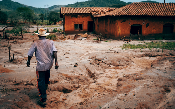 Um agricultor caminha por Paracatu de Baixo,uma das comunidades destruidas pela lama (Foto:  YASUYOSHI CHIBA/AFP)