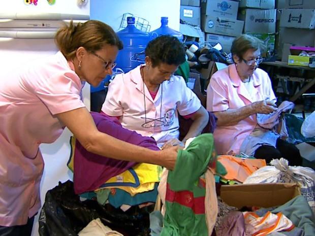 Voluntárias separam peças de roupas doadas para encaminhas ao bazar  (Foto: Antonio Luiz/EPTV)