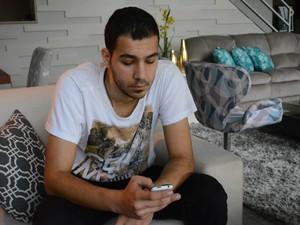 Celular ajuda o jovem de 25 anos a se comunicar com a família que ficou na Síria (Foto: Maiara Barbosa/ G1)