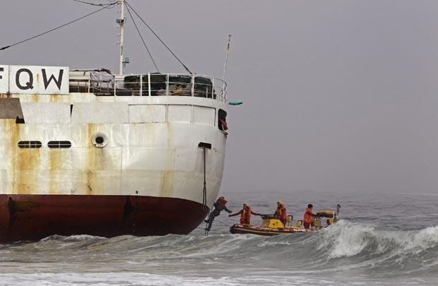 Pescadores são resgatados da traineira neste sábado (12) na costa da Cidade do Cabo (Foto: AP)
