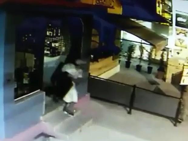 Após arrombar loja, criminoso sai com televisão embaixo dos braços (Foto: Imagens de câmeras de segurança)