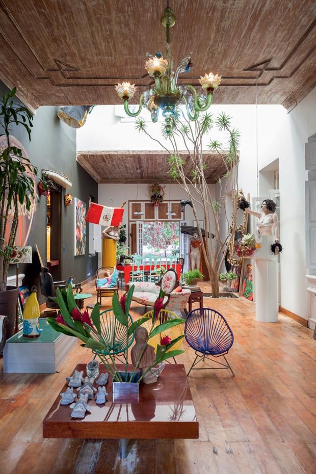 No salão principal, o que me encantou foi sua dimensão e pé-direito alto. Além do lustre e da textura do teto, observe a árvore plantada no meio da sala, o sofá florido e as esculturas provocantes. (Foto: Lufe Gomes/Lufe by Lufe)