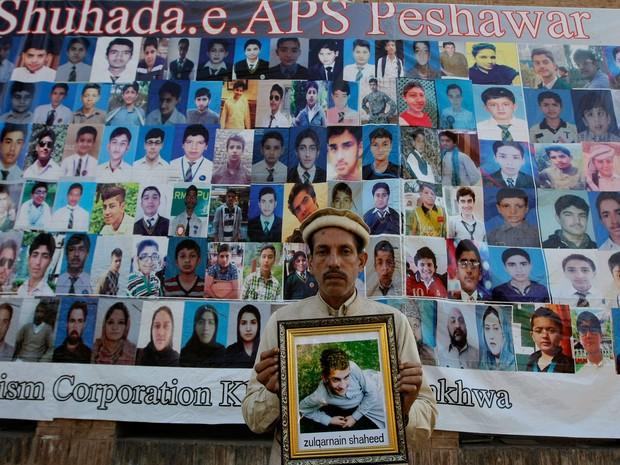 Pai segura foto de filho morto em ataque a escola em homenagem nesta quarta-feira (16) às vítimas do ataque a um escola em Peshawar, no Paquistão (Foto: Mohammad Sajjad/AP)