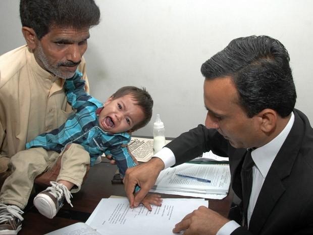 Muhammad Musa Khan chora enquanto suas impressões digitais são colhidas em Lahore na quinta-feira (3) (Foto: AFP)