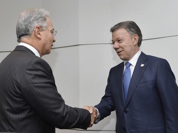O senador e ex-presidente Álvaro Uribe (à esquerda) cumprimenta o presidente Juan Manuel Santos nesta quarta-feira (5) no palácio presidencial em Bogotá (Foto: Efrain Herrera/Colombia's presidencial press office via AP)