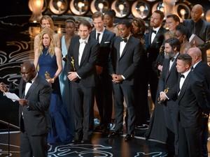 """O diretor Steve McQueen discursa ao ganhar o Oscar de melhor filme, à frente do elenco e produtores de """"12 anos de escravidão"""" (Foto: John Shearer/Invision/AP)"""
