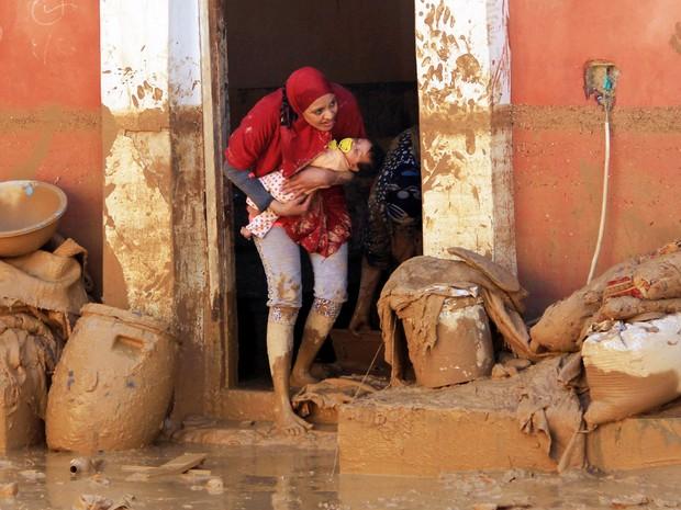 Em foto de 29 de outubro, mulher carrega um bebê depois das inundações em Ras Gahrib, perto da foz do Golfo de Suez, no Egito (Foto: Mostafa El-Shemy/AFP)
