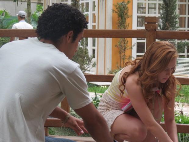 Gaby esbarra no rapaz e o ajuda a recolher cacos de vidro (Foto: TV Globo)