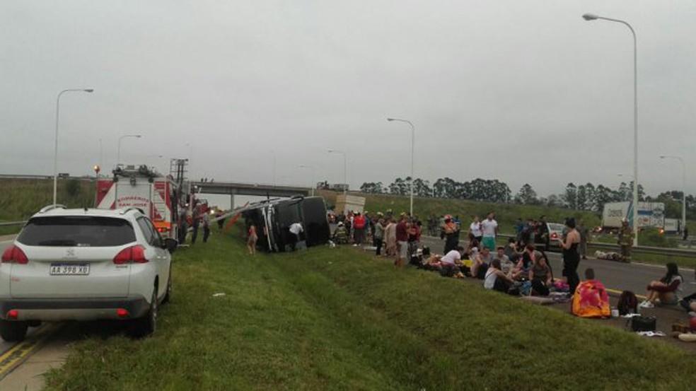 Passageiros são vistos ao lado de ônibus tombado  (Foto: Verônica Univaso/LT15/UNO Entrerios)