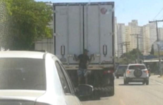 Homem se pendura na traseira de caminhão na Avenida Perimetral Norte, em Goiânia (Foto: Reprodução/ TV Anhanguera)